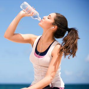 young teenager drinking water after exercise.